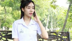 Portrait of thai student teen beautiful girl Answer the phone and smile. Stock Footage