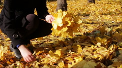 Happy girl in autumn park throws yellow fallen leaves - stock footage