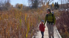 A family walking on boardwalk through botanical garden - stock footage