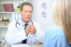 Smiling cardiologist talking to the patient - stock photo