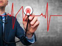 Business man  worker listening to heart beat with stethoscope Stock Photos