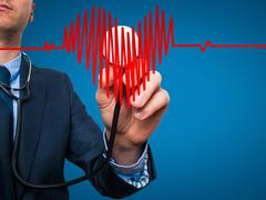 Business man  worker listening to heart with stethoscope - stock photo