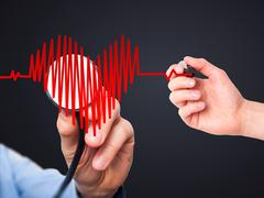 Doctor hand listening to heart beat in heart shape with stethoscope - stock photo