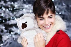 Christmas woman smiling with gift, owl plush toy, - stock photo