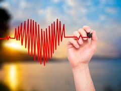 Closeup of hand drawing heart beat in heart shape with stethoscope - stock photo