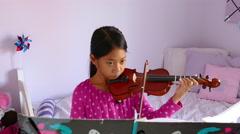 Little Asian Girl Practising Violin In Lavendar Bedroom Stock Footage