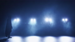 Male dancer is walking on a dark stage from left to right Stock Footage