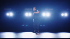 Caucasian male dancer in a vest and wide trousers is dancing on a dark stage - stock footage