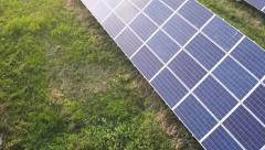 Aerial shot of solar farm at sunset moving forward, tight shot. - stock footage