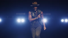 African american male in a hat is singing and dancing on a dark stage - stock footage