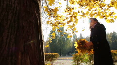 A girl throws yellow leaves from the tree branches of trees in autumn park - stock footage