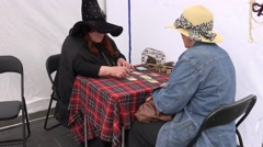 Witch turn tarot cards on table to women outdoor . 4K Stock Footage