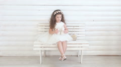 Cute little girl sitting on a bench and playing with plush toys Stock Footage