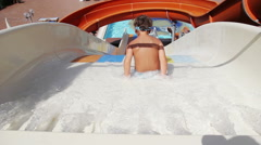 Young Boy Riding On White Water Slide To The Pool. Aquapark, Water Park - stock footage