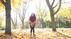 Teen age young girl in autumn park throw a yellow fallen leaves up in air - stock footage