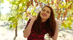 Stock Video Footage of Beautiful curly hair young girl walking happy and glad in an autumn park nature