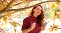Young smile red head girl take a shot via smart phone of yellow autumn leaves Footage
