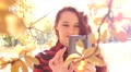 Young cute red head girl take a shot via smart phone of yellow autumn leaves Footage