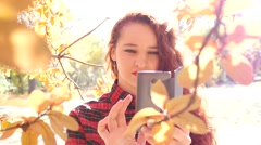 Young cute red head girl take a shot via smart phone of yellow autumn leaves Stock Footage