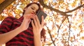 Young red head girl type slide her smart phone in an autumn park nature Footage