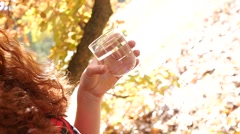 Young woman drinking clean pure water from glass on nature autumn light haze Stock Footage