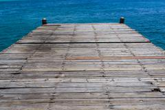 wooden bridge juts out into  of the sea - stock photo