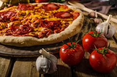 Rustic salami pizza with cheddar cheese and chorizo Stock Photos