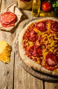 Rustic salami pizza with cheddar cheese and chorizo - stock photo