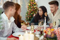 Friends enjoying christmas dinner together Stock Photos