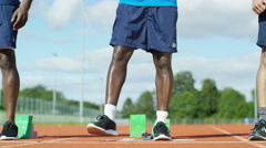 4K Portrait of black athlete getting into position at running track Stock Footage