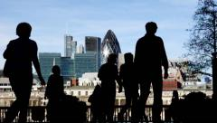 Silhouetted people walk against a London skyline Arkistovideo