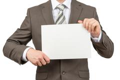 Businessman holding blank paper on white - stock photo