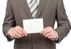 Businessman holding small blank sheet of paper Stock Photos