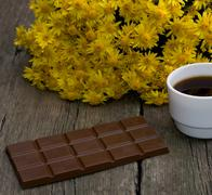 bouquet of yellow flowers, tile a chocolate and coffee, on a wooden table, a - stock photo