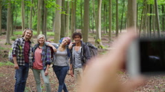 4K Group of friends hiking in the woods pose to take a photograph Stock Footage