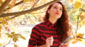 Young smile red head girl take a shot via smart phone of yellow autumn leaves 4k or 4k+ Resolution