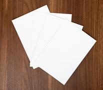 Four blank cards on wood table, top view Stock Photos