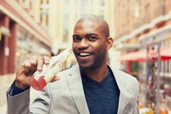 young smiling man drinking soda from glass bottle - stock photo