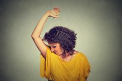 Woman, smelling, sniffing her wet armpit, something stinks, very bad foul odo Stock Photos