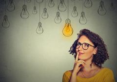 thinking woman in glasses looking up with light idea bulb above head - stock photo