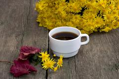 bouquet of yellow flowers, coffee, red leaf and floret, on a wooden table, fa - stock photo