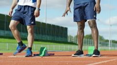 4K 2 athletes get into position at running track starting line before a race - stock footage