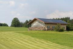 Alternative energy creation at a farm with solar panels on the roor - stock photo