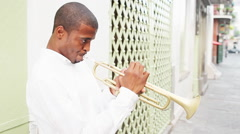 Black man plays a trumpet in the street - stock footage