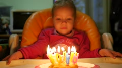 Home birthday family party little kid girl blows candles on a cake slow motion Stock Footage