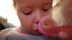 Little kid girl drink the beverage from a baby bottle with a nipple closeup Arkistovideo