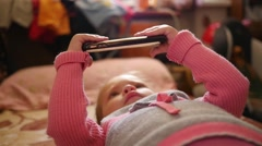 Little kid girl watch a smart phone cartoons lying on a couch in the morning  Stock Footage