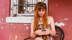 Young woman sits outside of a building and texts on her phone - stock footage