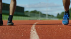 4K Low angle view, 2 unrecognisable athletes at running track Stock Footage