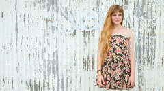 Young woman stands in front of a wall with peeling paint and poses Stock Footage